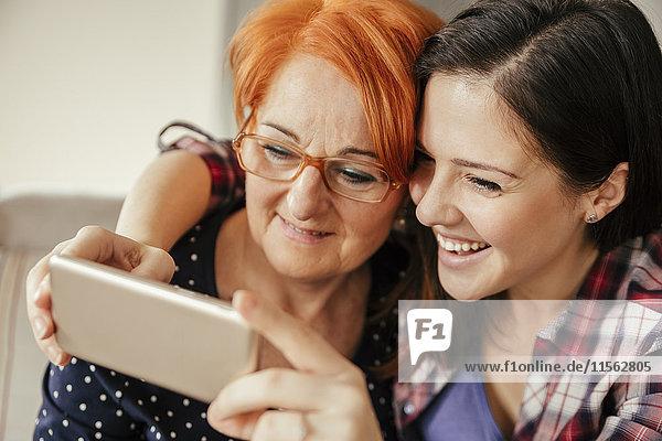 Glückliche erwachsene Tochter mit Mutter  die einen Selfie nimmt.