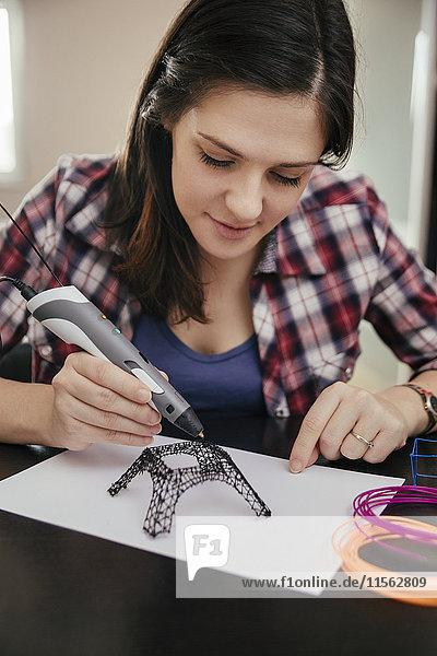 Junge Frau zeichnet Eiffelturm mit 3D-Stift