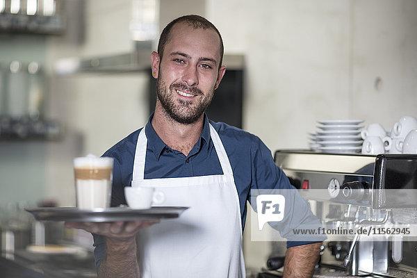Porträt des lächelnden Barista mit Latte Macchiato
