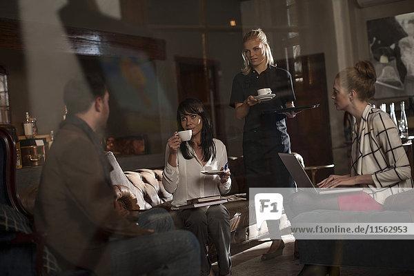 Kellnerin  die den Geschäftsleuten Kaffee serviert  um zu diskutieren