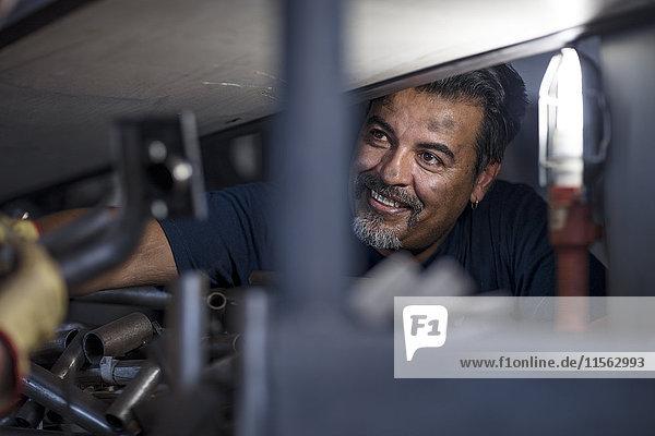 Smiling mechanic working on motorcycle in workshop