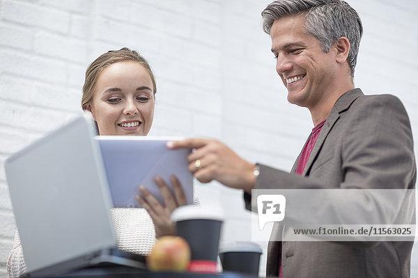 Geschäftsmann und Frau bei einem Treffen mit Blick auf das digitale Tablett