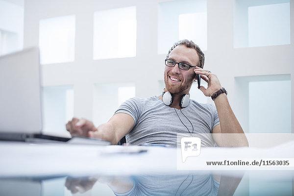 Junger Mann mit Kopfhörern um den Hals spricht am Telefon