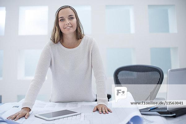 Junge Frau am Schreibtisch stehend mit Laptop und digitalem Tablett
