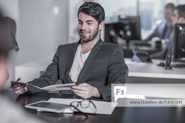 Lächelnder Mann schaut auf Booklet am Schreibtisch im Stadtbüro