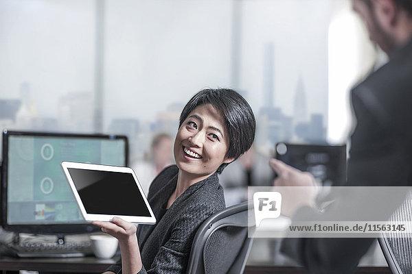 Lächelnde Frau zeigt Tablette an Kollegen im Stadtbüro