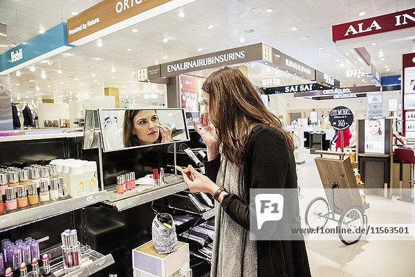 Sweden,  Woman testing foundation in perfumery