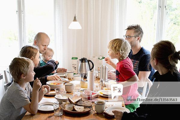 Schweden  Familie mit Kindern (2-3  4-5 10-11 16-17) beim Frühstück am Tisch