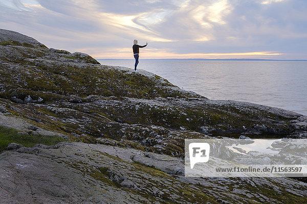 Schweden  Ostergotland  Stora Lund  Frau steht auf Felsen und fotografiert Meer