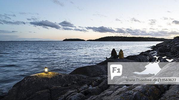 Schweden  Sodermanland  Braviken  Teenage Girl (16-17) sitzend mit junger Frau am Meer in der Abenddämmerung.