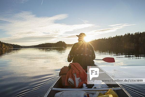 Schweden  Skane  Raslangen  Rückansicht des Mannes Paddelboot auf dem See