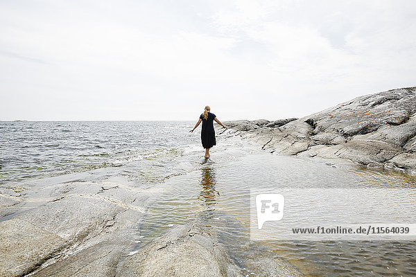 Sweden  Stockholm Archipelago  Sodermanland  Huvudskar  Rear view of mature woman wading in sea