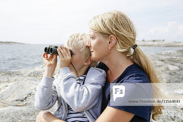 Schweden  Stockholm Archipel  Sodermanland  Orno  Mutter und Sohn (6-7) sitzen am felsigen Ufer  Sohn schaut durchs Fernglas.