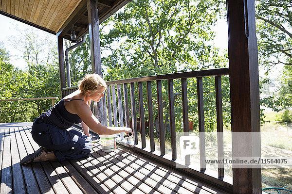 Sweden  Stockholm Archipelago  Sodermanland  Orno  Mature woman painting porch railing