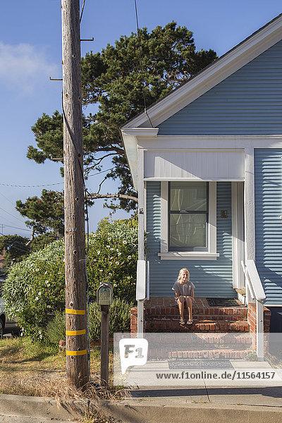 USA  Kalifornien  Pacific Grove  Mädchen (12-13) sitzend auf Stufen vor blauem Haus