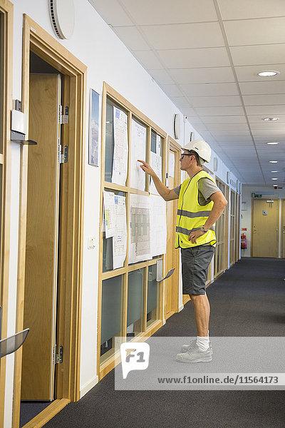 Schweden  Mann in Schutzkleidung im Flur stehend und auf an der Wand hängende Papiere zeigend