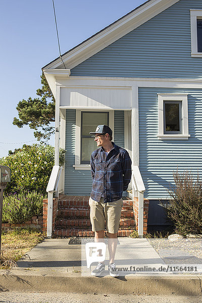 USA  California  Pacific Grove  Mature man standing in front of blue house