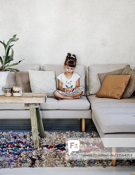 Schweden,  Mädchen (4-5) sitzend auf Sofa