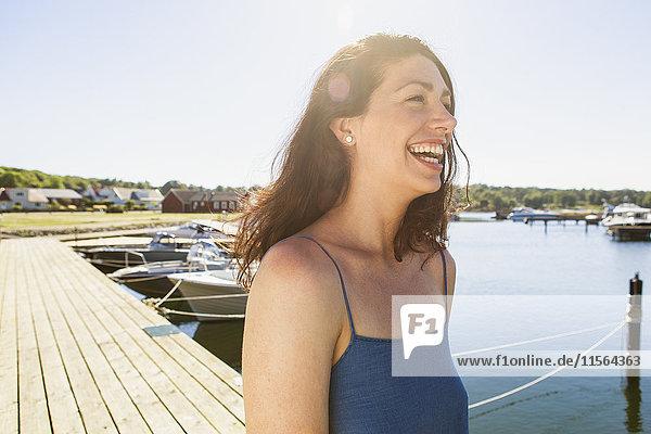 Schweden  Blekinge  Horvik  Fröhliche Frau  die am Pier spazieren geht