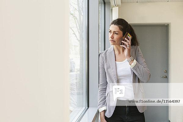 Schweden  Geschäftsfrau schaut durchs Fenster und nutzt Smartphone