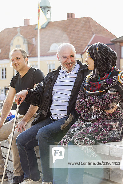 Sweden  Bleking  Solvesborg  Portrait of people sitting on brick wall