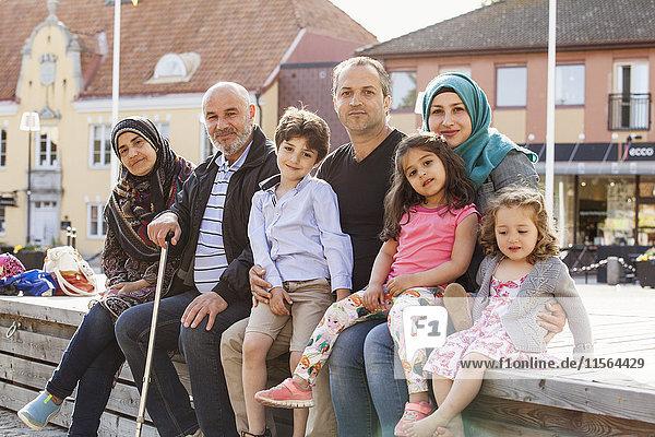 Schweden  Blekinge  Solvesborg  Porträt einer Familie mit Kindern (2-3  4-5  6-7) auf Ziegelwand sitzend