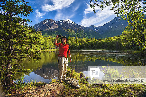 Hiker taking a selfie next to Dew Pond in the Chugach State Park near Eagle River  Southcentral Alaska  summer