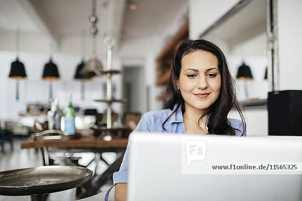 Germany  Pleased woman using computer
