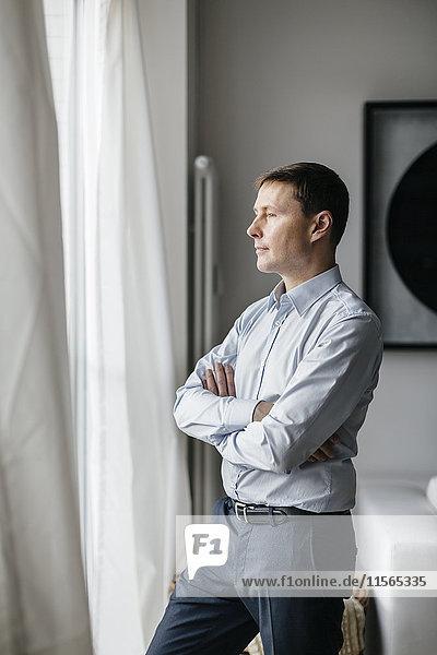 Deutschland  Mann schaut durchs Fenster