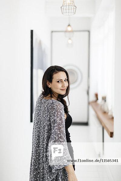 Germany  Woman looking over shoulder in corridor