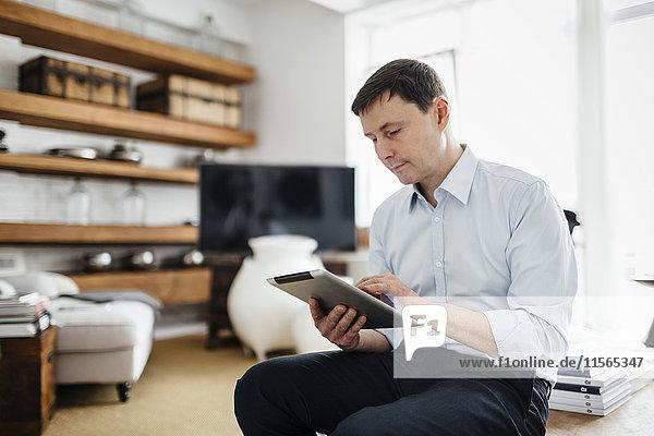 Deutschland  Mann mit Tablette im Wohnzimmer
