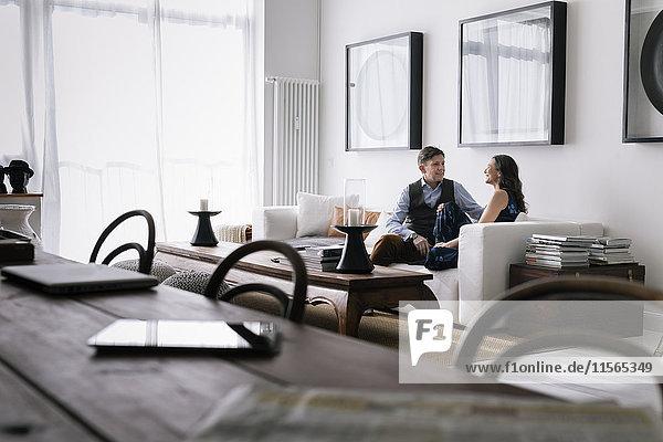Deutschland  Paar sitzend auf Sofa im Wohnzimmer