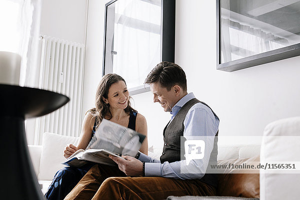 Germany  Couple sitting on sofa and reading book
