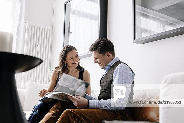Deutschland  Paar sitzt auf Sofa und liest Buch