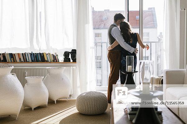 Deutschland  Paarumarmung am Fenster im Wohnzimmer