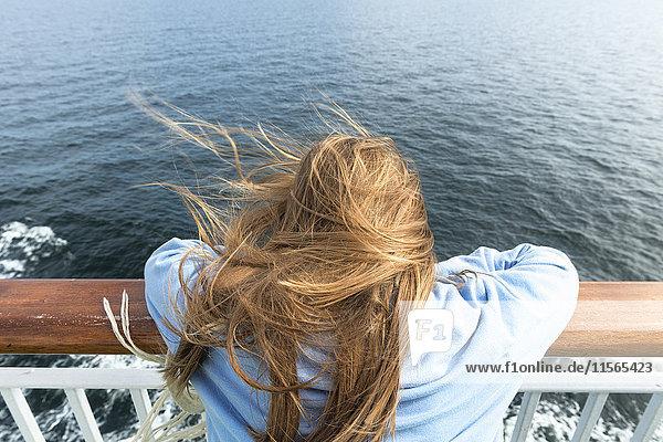 Schweden  Sodermanland  Rückansicht eines blonden Mädchens (10-11)  das sich auf ein Geländer auf einem Kreuzfahrtschiff stützt.
