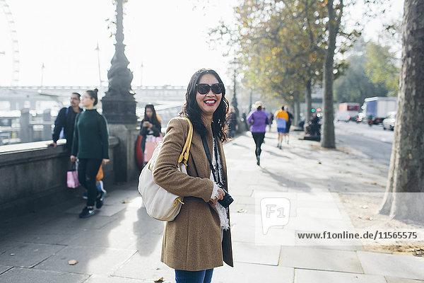 UK  England  London  Lächelnde Frau steht auf dem Bürgersteig am Victoria-Damm