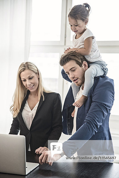 Father giving daughter piggyback and looking with woman at laptop