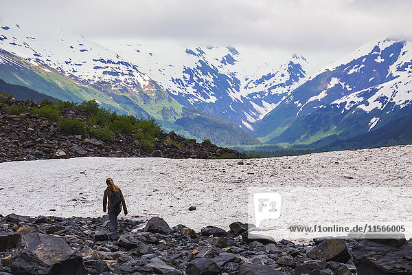 'A teenage girl hikes off-trail near Byron Glacier in Portage Valley on a rainy day in early summer; Alaska  United States of America'
