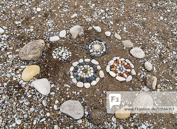 'Designs made with various coloured rocks in the sand on the beach; South Shields  Tyne and Wear  England'
