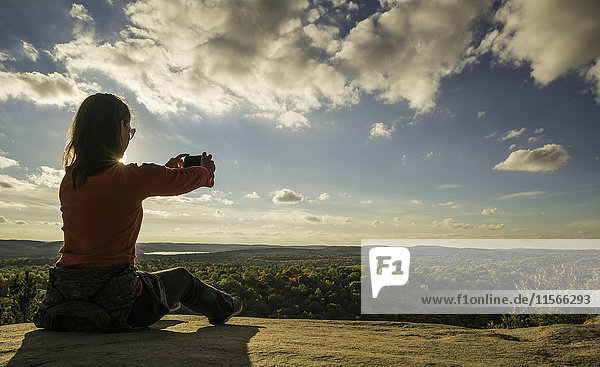 'Woman taking photos with a smart phone in Algonquin Park; Ontario  Canada'