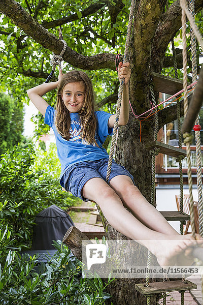 'A smiling young girl wearing a blue t-shirt  sitting outside on a rope ladder in a tree; Darmstadt  Hessen  Germany'