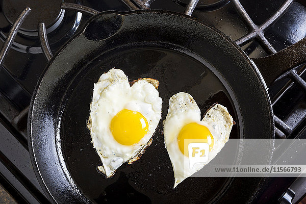 'Close up of heart shaped sunny side up eggs in a cast iron frying pan; Calgary  Alberta  Canada'