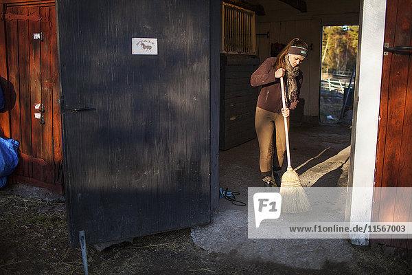 Schweden  Uppland  Faringso  Frau fegt in Scheune