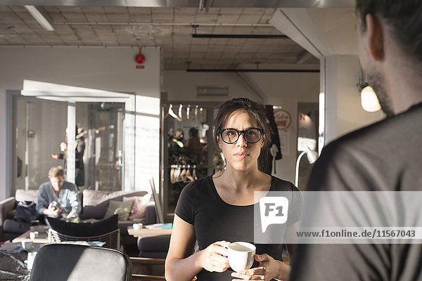 Woman holding coffee cup in office