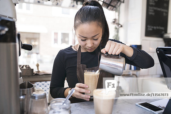 Woman preparing coffee in cafe