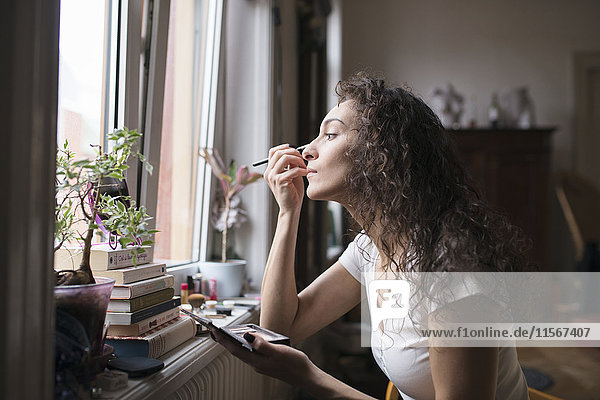Woman doing her makeup by the window.