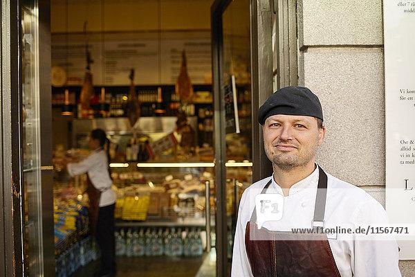 Schweden  Mann in Schürze steht vor dem Geschäft
