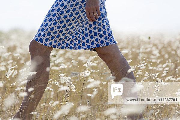 Woman walking through meadow