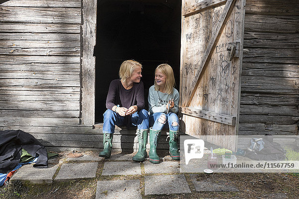 Girl and teenage boy sitting in front of barn